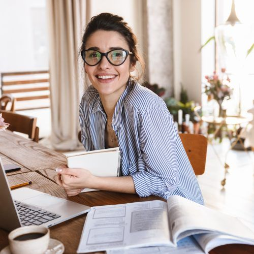 Image of cute young woman 20s in casual clothing typing on laptop while working or studying at home