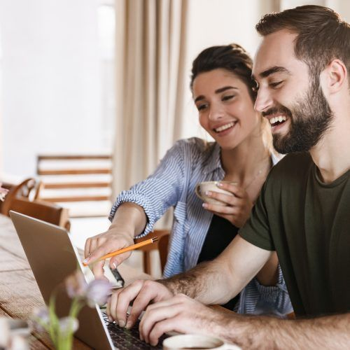 Image of pretty brunette couple man and woman 20s drinking coffee and working on laptop together while sitting at table at home